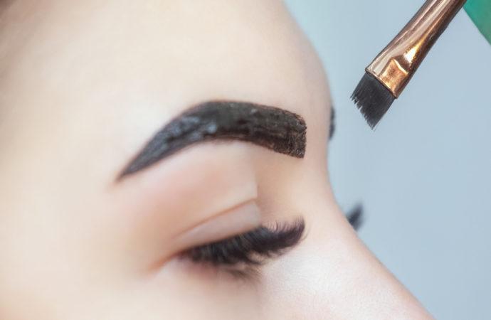 makeup artist applies paint henna on eyebrows in a beauty salon.